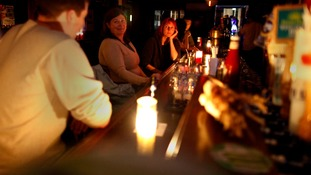 Patrons drink at a bar and use only candlelight in the aftermath of Hurricane Sandy in New York.