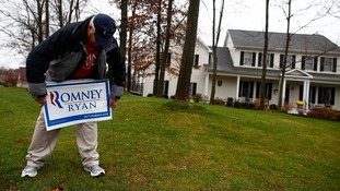 Volunteer Jeff Johnson installs a sign while canvassing for U.S. Republican presidential candidate Mitt Romney in Columbus, Ohio