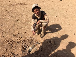 A Iraqi Army soldier is seen in front of an uncovered landmine.