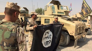 Iraqi forces hold aloft an Islamic State flag left behind by retreating militant fighters.