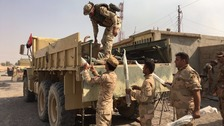 The Iraqi Army load a truck with weapons left behind by IS fighters.