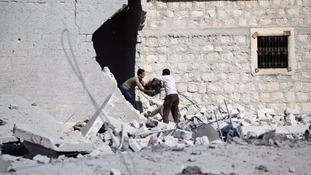 Men carry their belongings from their damaged home in Aleppo.