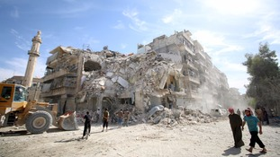 People inspect bomb damage in the rebel-held part of Aleppo