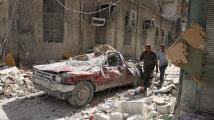 Residents walk past a ruined car in the rebel-held half of Aleppo