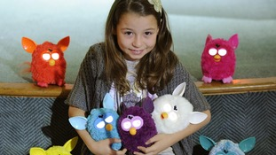 A child poses with Furby toys