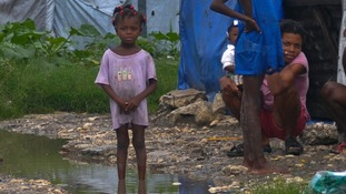 A Haitian girl stands in dirty water after heavy rains from Hurricane Sandy flooded her tent encampment