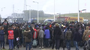 Residents of the 'Jungle' camp queue for buses.