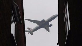 A plane flies over homes near Heathrow.