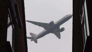 A plane flies over homes near Heathrow