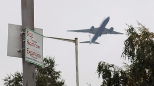 A plane flies past a Stop Heathrow Expansion sign.