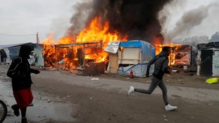 A migrant sprints past the makeshift homes which are on fire