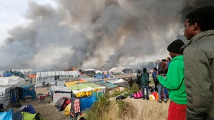Smoke billows from the raging fires in the camp