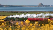 A steam trains rolls through the Northumberland countryside - passing Holy Island in the distance