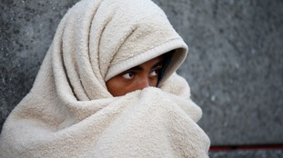 A girl is seen covering herself with a blanket.