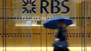File photo of a woman walking past the headquarters of the Royal Bank of Scotland in the City of London
