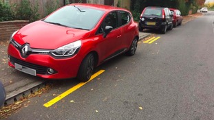 Double yellow lines fail: Workers paint around parked cars