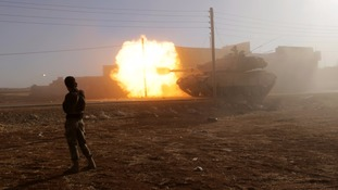 A rebel fighter stands near a Turkish tank as it fires