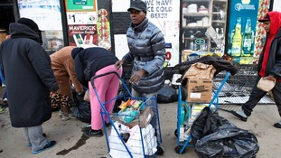 People look for salvageable food discarded from a flooded store in Coney Island, New York, on Friday.