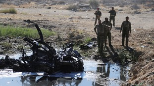 Iraqi security forces inspect the site of the Tikrit blast
