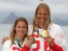 Hannah Mills and Saskia Clark (right) celebrate on the podium with their gold medals from the Women's 470 Race