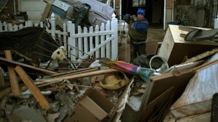 A man carries his belongings to a pile outside his house, which was left flooded by hurricane Sandy, in Staten Island