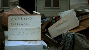 A message is left on flooded belongings outside a house hit by hurricane Sandy