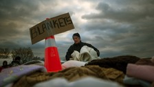 A victim of hurricane Sandy takes blankets from a aid distribution site in the Staten Island