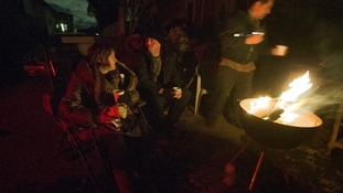 Victims of hurricane Sandy sit near a fire to stay warm outside their destroyed homes in Staten Island
