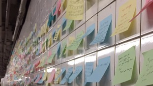 Colourful post-it notes with inspirational messages cover the subway wall in Manhattan.