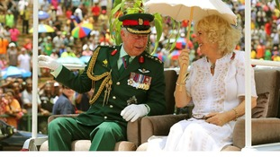 The Prince of Wales and Duchess of Cornwall are driven on the back of a truck visit