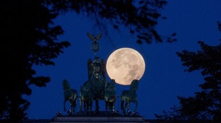 The perigee full moon, or supermoon, appears red behind the quadriga of the Brandenburg Gate in Berlin, Germany, 28 September 2015