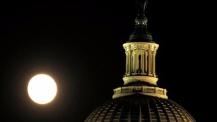 The supermoon rises over the US Capitol dome in Washington.
