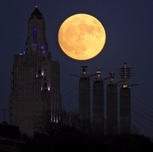 The 'supermoon' rises over the Power and Light building in Kansas City, Missouri.