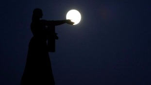 The 'supermoon' rises over La Raza monument, in Ciudad Juarez, Mexico.