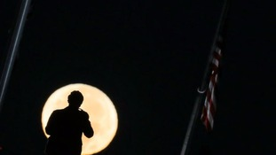 A man takes a picture of the 'supermoon' over the National Mall in Washington.