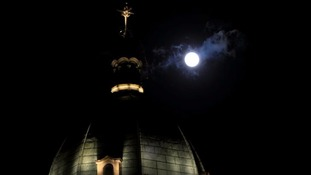 The 'supermoon' shines behind a cross of a catholic church in metro Manila, Philippines.
