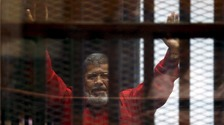 Mohamed Morsi greets his supporters from behind bars at a court hearing in June.