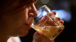 A file photo of a woman drinking a glass of beer.