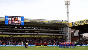 Players and fans observe a minute's silence.