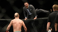 McGregor scales the octagon to celebrate with Lobov.
