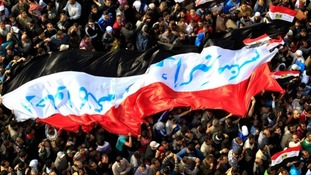Egyptian protesters march with a huge flag during a rally at Tahrir Square in Cairo in 2011.