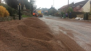 Residents help clear main road blocked with sand after torrential rain