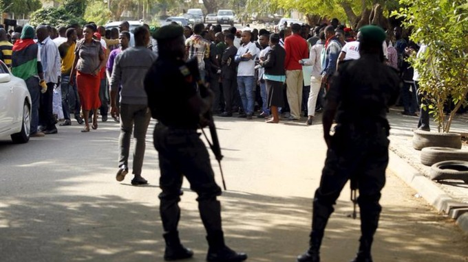 Policemen stand guard as supporters of Indigenous People of Biafra (IPOB) leader Nnamdi Kanu take part in a rally in December 2015.