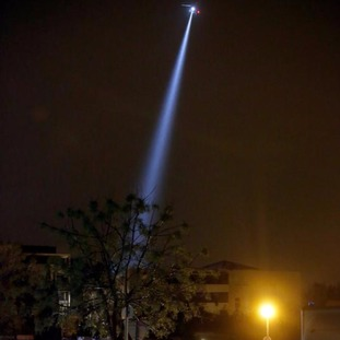 A police helicopter searches for the suspect.