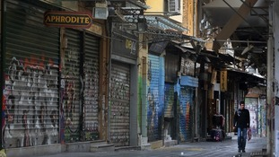 A man walks through an empty commercial street in Athens