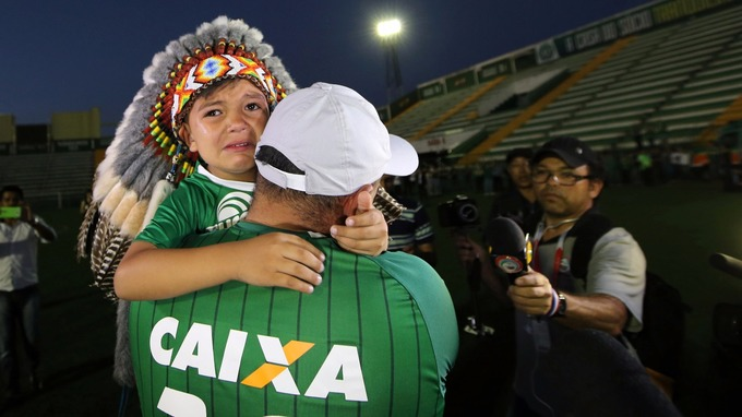 A young Chapecoense supporter is held by his father as he is interviewed on the pitch.
