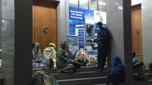 Zimbabweans queue overnight for banks to open hoping to secure some of the country's shrinking store of US dollars.