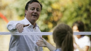 David Cameron with his young badminton competitor.