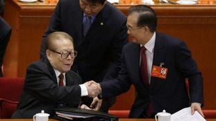 China's former President Jiang shakes hands with Premier Wen.