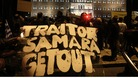 A protester holds a banner reading &quot;Traitor Samara get out&quot;(Greece&#x27;s Prime Minister Antonis Samaras )in front of the parliament .